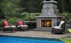 stone outdoor fireplace by pool